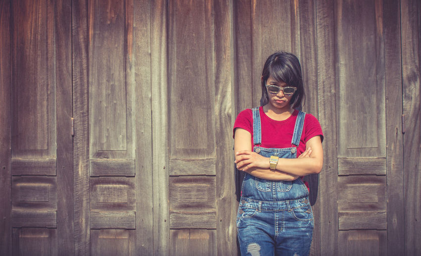 Woman with sunglasses standing against wall during sunny day