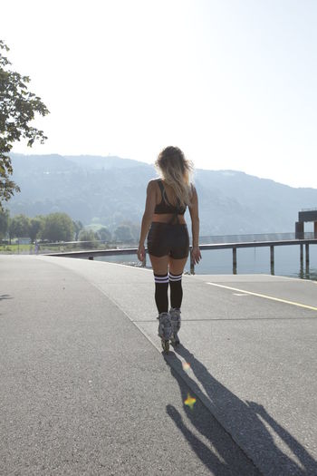 Rear view of woman inline skating on road
