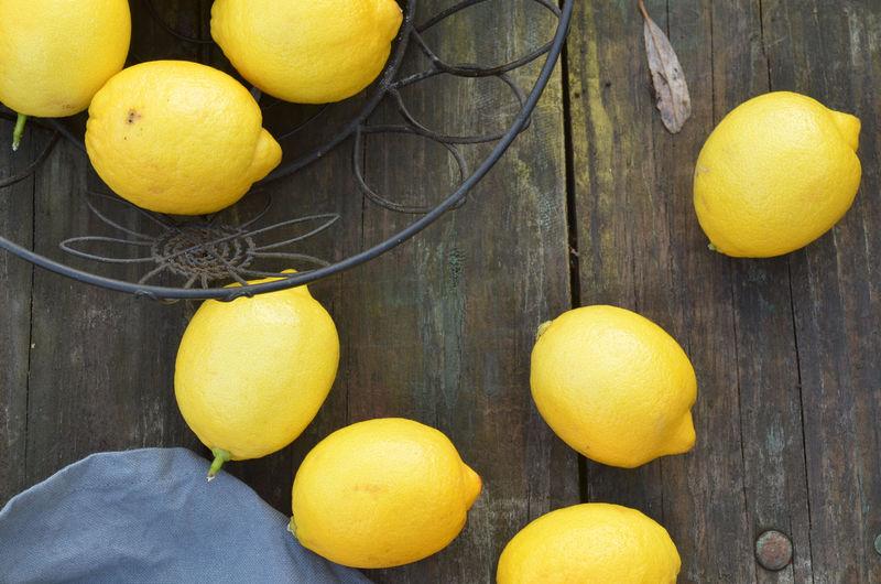 fresh lemons on rustic wood tabletop Backgrounds Citrus Fruit Day Food Fresh Fruit Fresh Produce Freshness Fruit Ingredient Lemon Lemons No People Preparing Food Wood Table Yellow