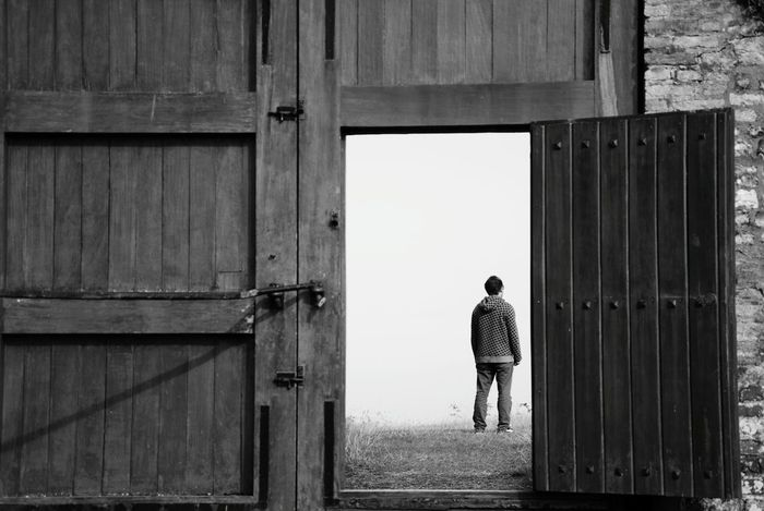 modern western Man Alone Normandie, France Wooden Door Door Open Staring Loneliness What's Next? Back Turned Timeless Fine Art Photography Black & White Still Showcase July People And Places. Outside Photography Finding New Frontiers Adapted To The City The Secret Spaces