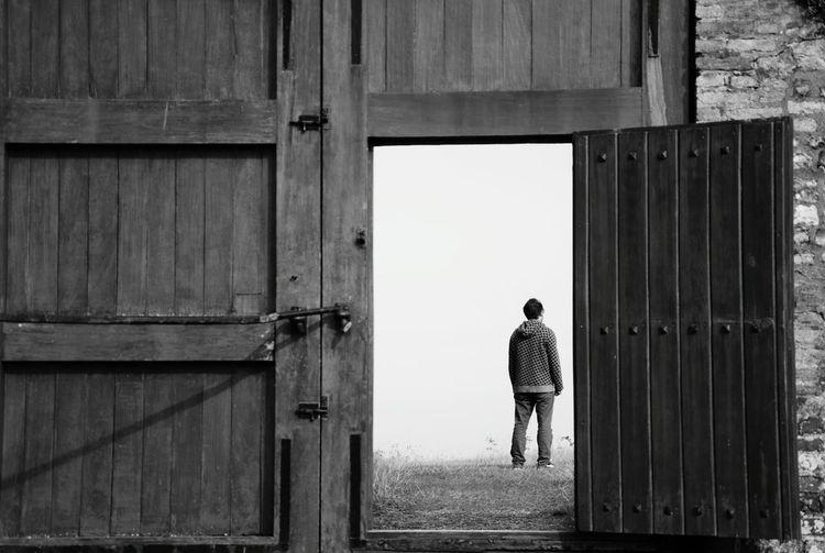 Rear View Of Man Standing On Field Seen Through Open Door