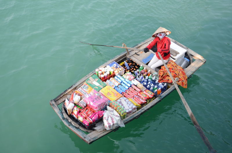 High angle view of woman selling food and drink on boat in river