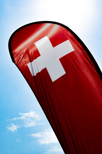 Swiss Banner Flag with Sunlight and Against Blue Sky in Switzerland. Red Sky Low Angle View Day Cloud - Sky No People Nature Close-up Outdoors Flag White Color Patriotism Shape Communication Symbol Sunlight Pride Swiss Flag Banner Banner - Sign Swiss Culture Sun Sunlight Backlit Colorful