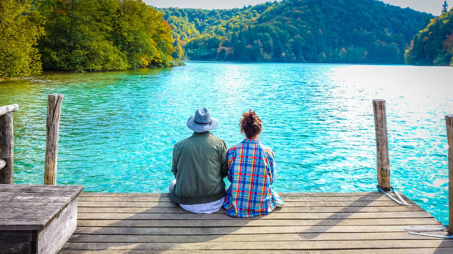 Rear View Of Couple Sitting On Jetty Over Lake