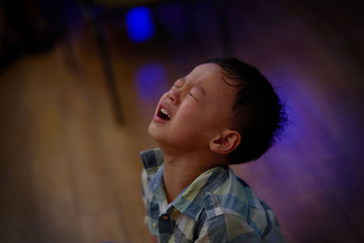 High angle view of cute boy crying on floor at home
