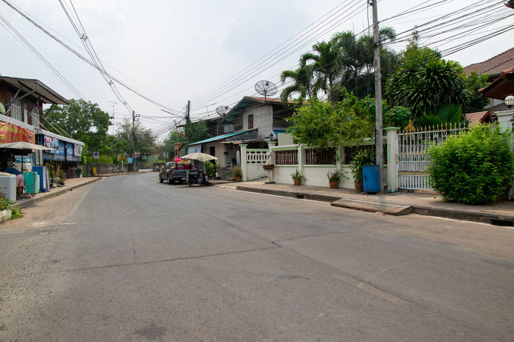 Street amidst houses and buildings against sky