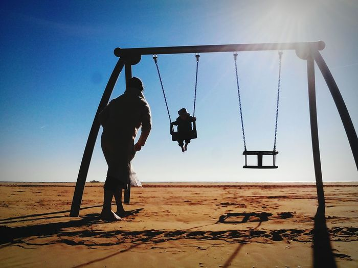 Child Swinging By Man At Beach Against Sky On Sunny Day