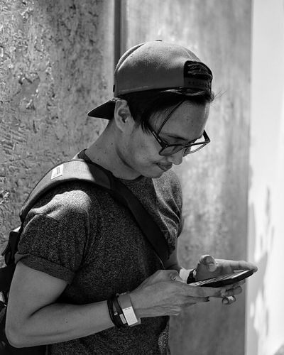 Fashionable Man Using Mobile Phone While Standing By Wall