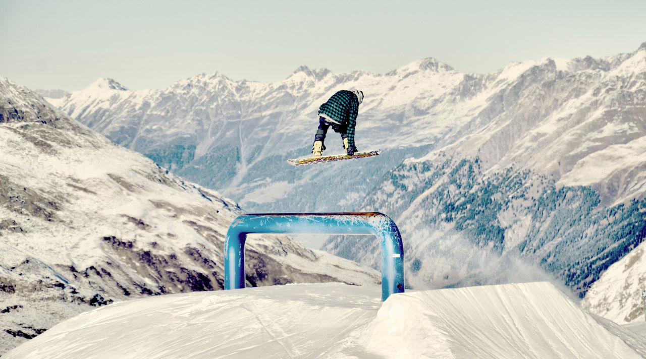 Rear view of man performing stunts while snowboarding on mountain top