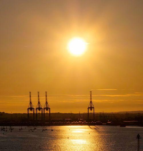 Sunset cranes Cranes Crane - Construction Machinery Sunset Sky Sun Water Orange Color Industry Sunlight Oil Industry Transportation Sea Silhouette