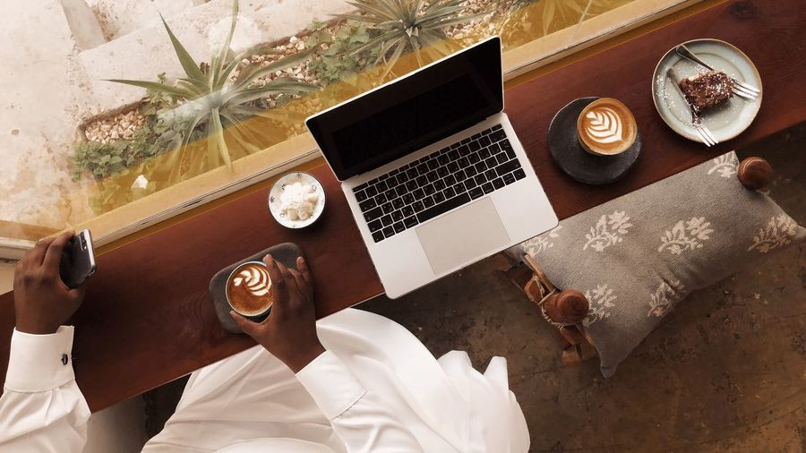 Midsection Of Man Holding Cappuccino By Laptop On Table In Cafe