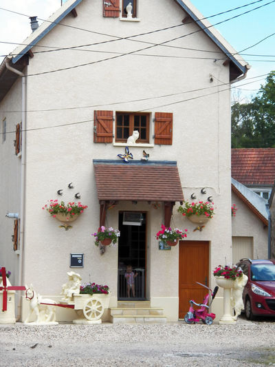 One frontage of a family house with special lot of sculpture and decorations. One House Tiny House  Crepy Frontage Charming Baby Sculpture Sculptures, Sculpture Donkey Windmill Birds Cat Dog Butterflies Toys Little Bike Door Open Big Baby Cable Day Front House Photography In France