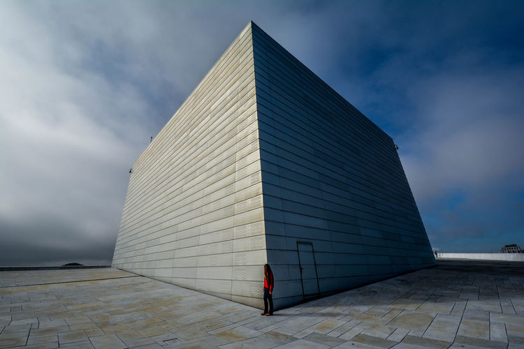 Side View Of Woman Standing At Oslo Opera House Against Cloudy Sky