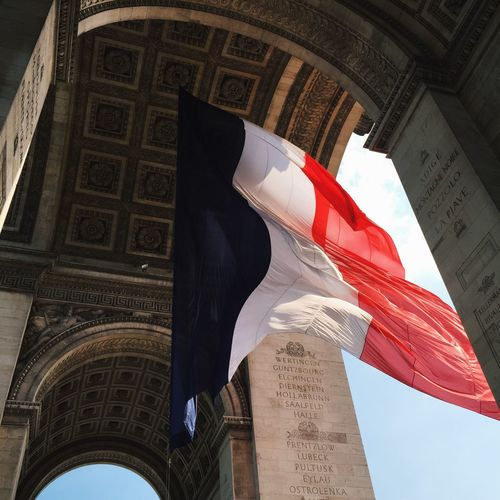 Low angle view of french flag waving in historic building