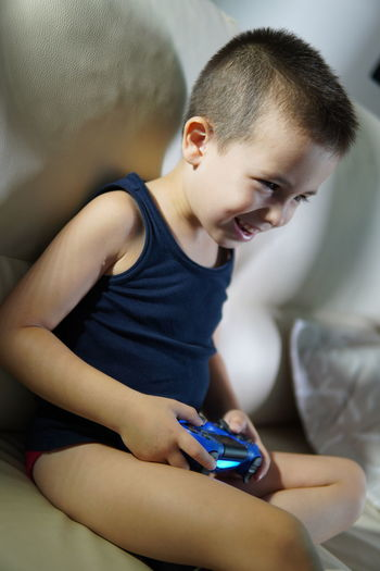 Smiling boy playing game while sitting on bed at home
