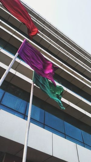 Low angle view of flags hanging on building against sky