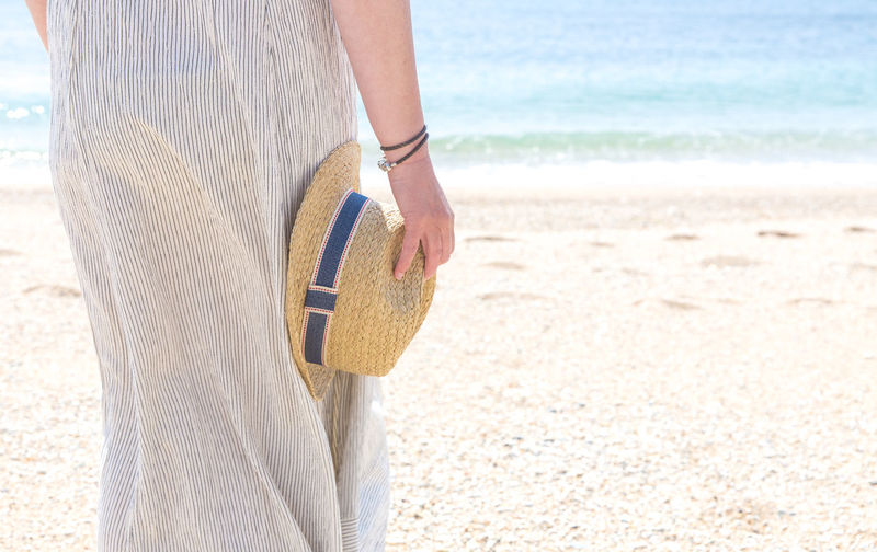 Midsection Of Woman Holding Hat While Standing At Beach