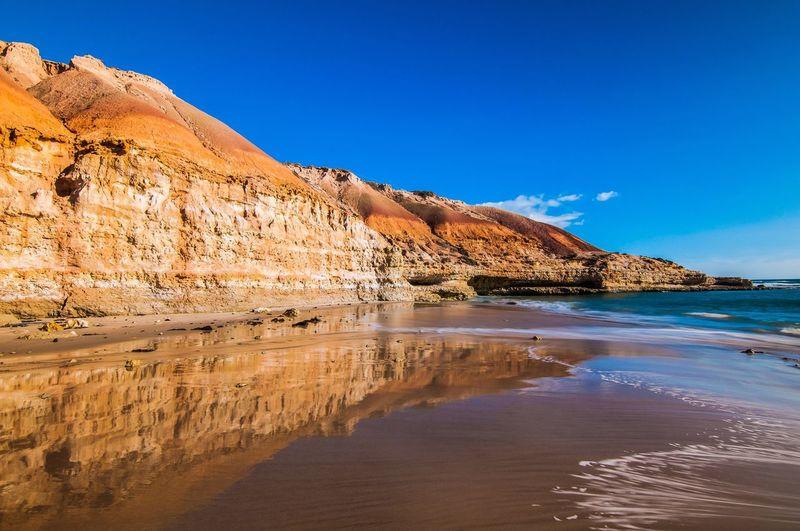 Scenic Reflection Of Rocky Landscape In Sea