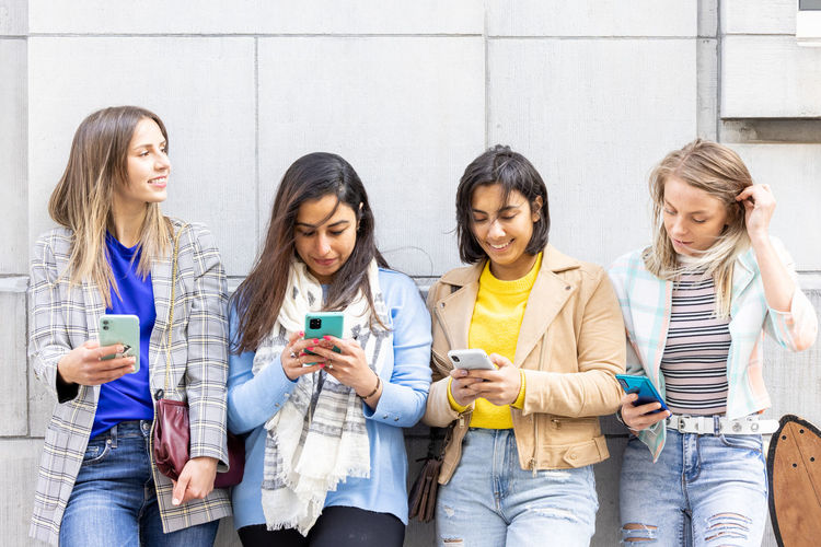 Group of friends standing on mobile phone