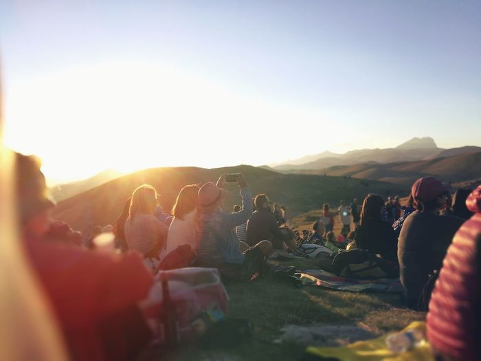 Group of people on mountain against sky during sunset