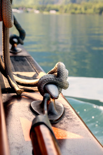 Rope tied up with cleat on boat in lake