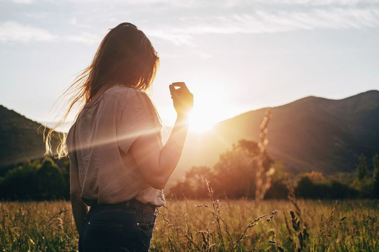 Woman photographing on field during sunset