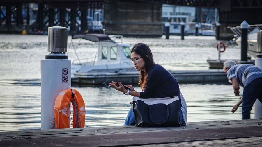 Woman using mobile phone while sitting on laptop