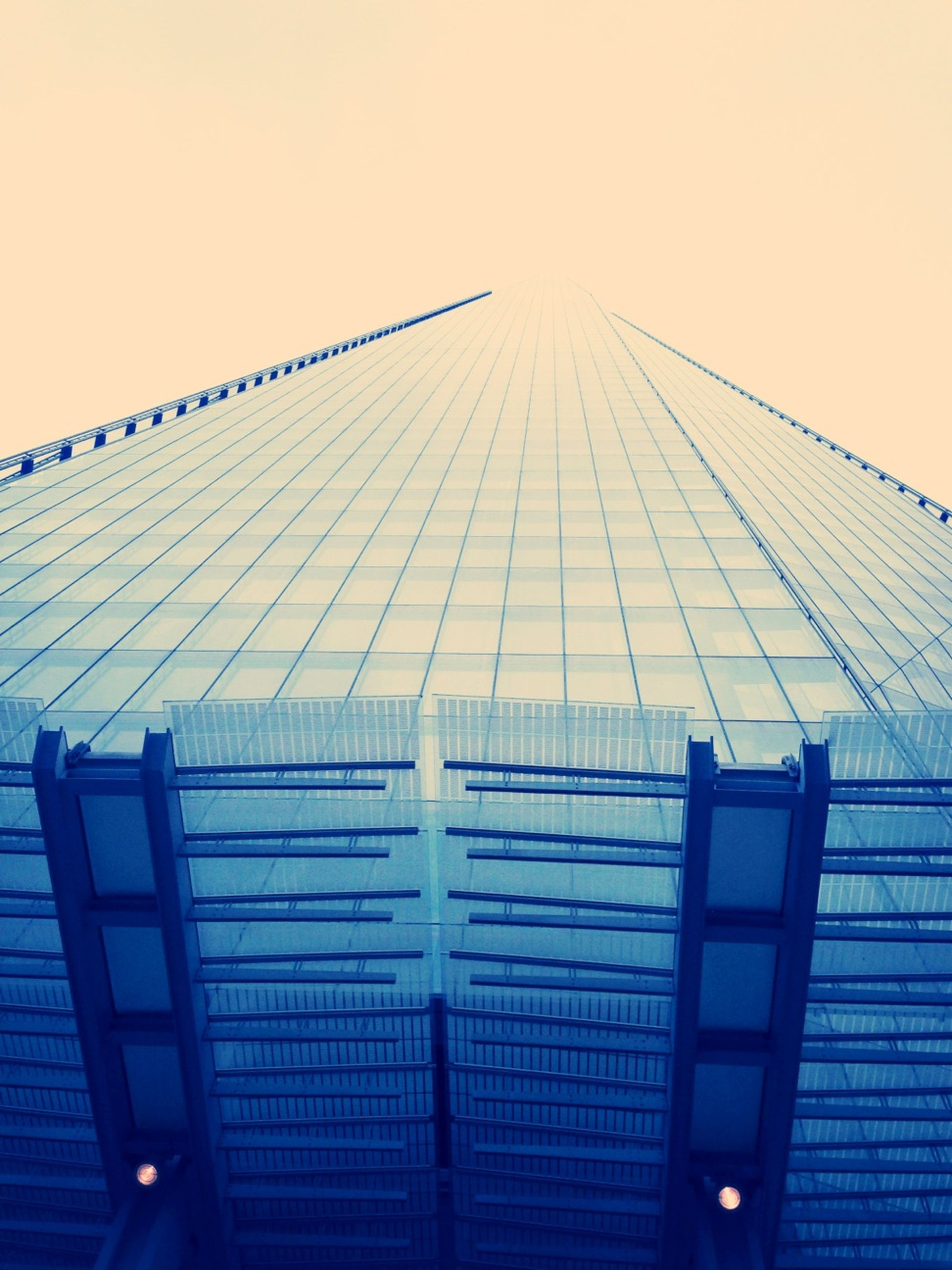 low angle view, architecture, built structure, clear sky, building exterior, modern, sky, office building, skyscraper, city, outdoors, day, no people, building, tall - high, copy space, development, pattern, glass - material, connection