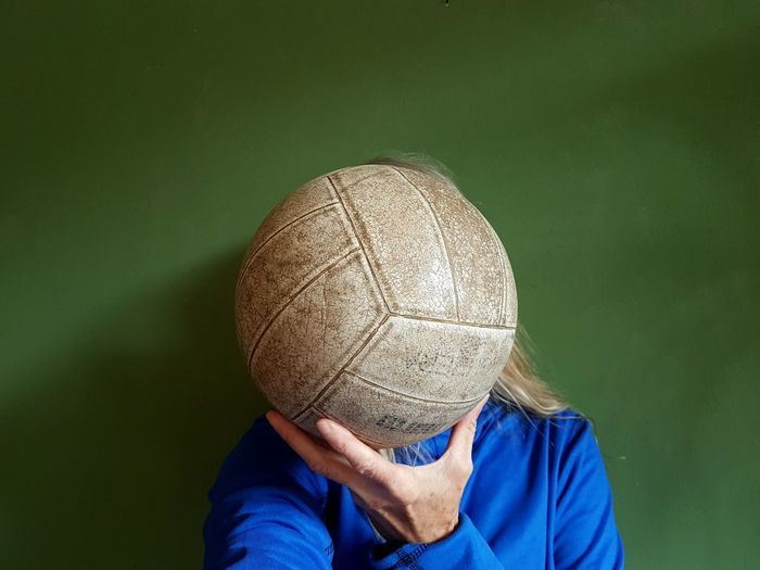Mature woman holding volleyball in front of face against blue covering face