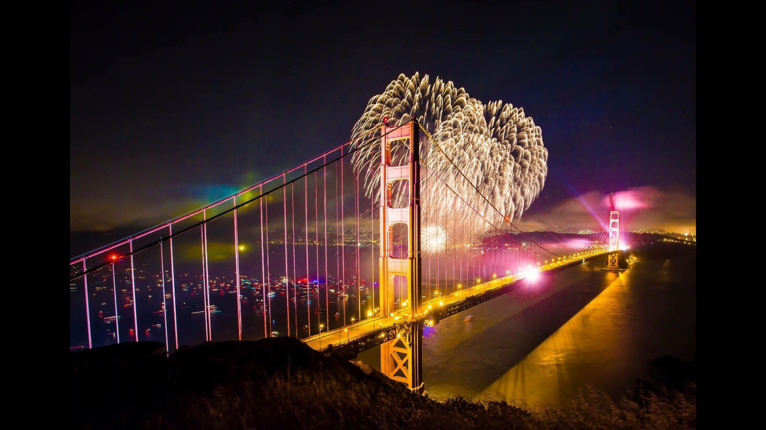 night, illuminated, built structure, architecture, long exposure, connection, clear sky, sky, arts culture and entertainment, bridge - man made structure, suspension bridge, motion, travel destinations, low angle view, outdoors, engineering, water, famous place, building exterior, red