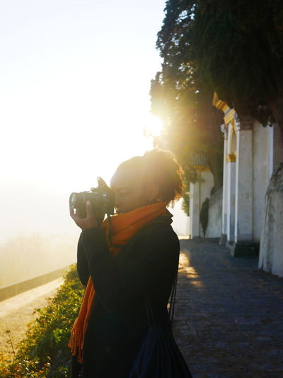 Rear view of man photographing at camera