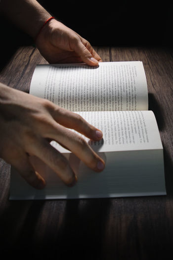 Close-up of woman reading book on table