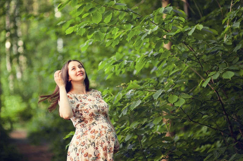 Pregnant woman looking away while standing against tree in forest