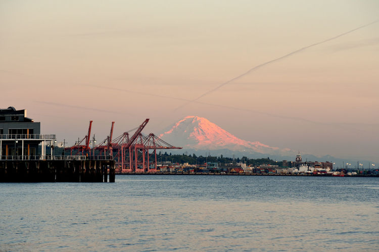 Mount rainier viewed from downtown seattle waterfront with port shipping cranes at dusk.
