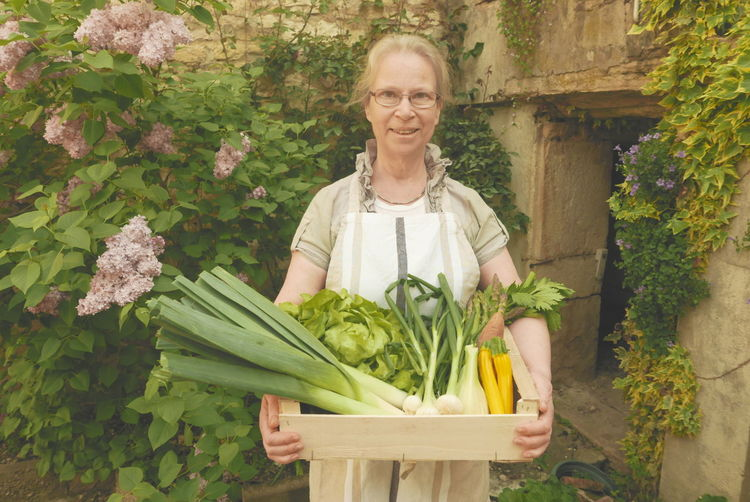 Portrait of smiling senior woman holding fresh vegetables in crate against plants