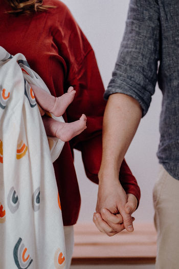Midsection of couple holding hands