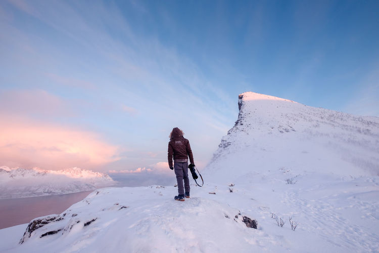 Rear view of person walking on snowcapped mountain against sky