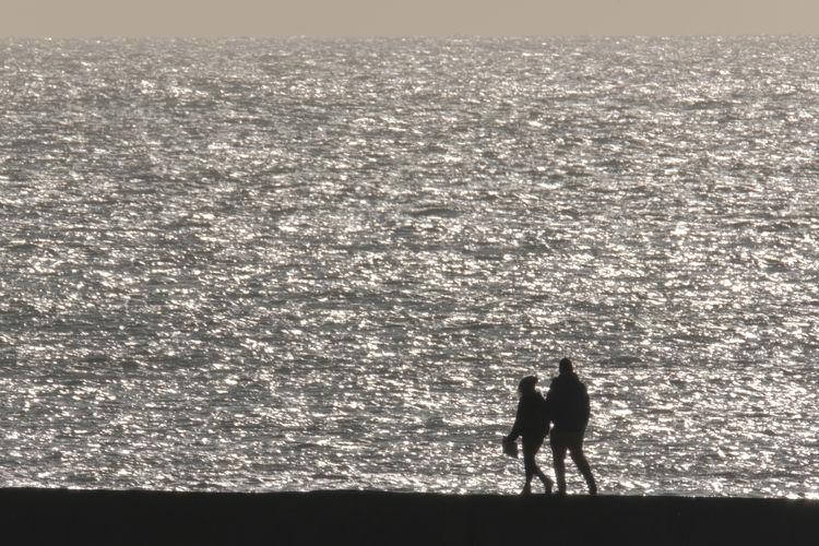 Silhouette men on beach against sky
