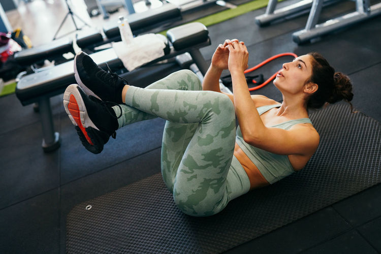 High angle view of woman exercising on mat in gym