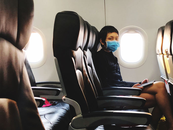 Woman wear surgical mask in airplane to protect virus