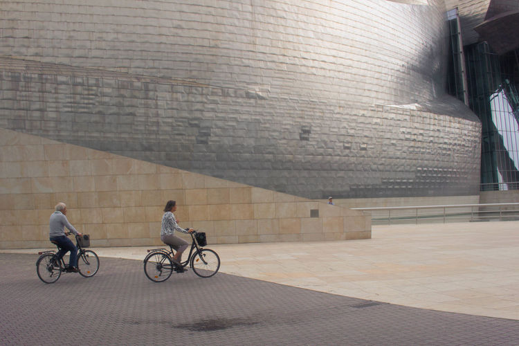 Adventures In The City Architecture Bicycle Building Exterior Built Structure City Full Length Gugenhain Museum Lifestyles Mode Of Transportation Motion People Riding Street Sunlight Transportation Wall - Building Feature