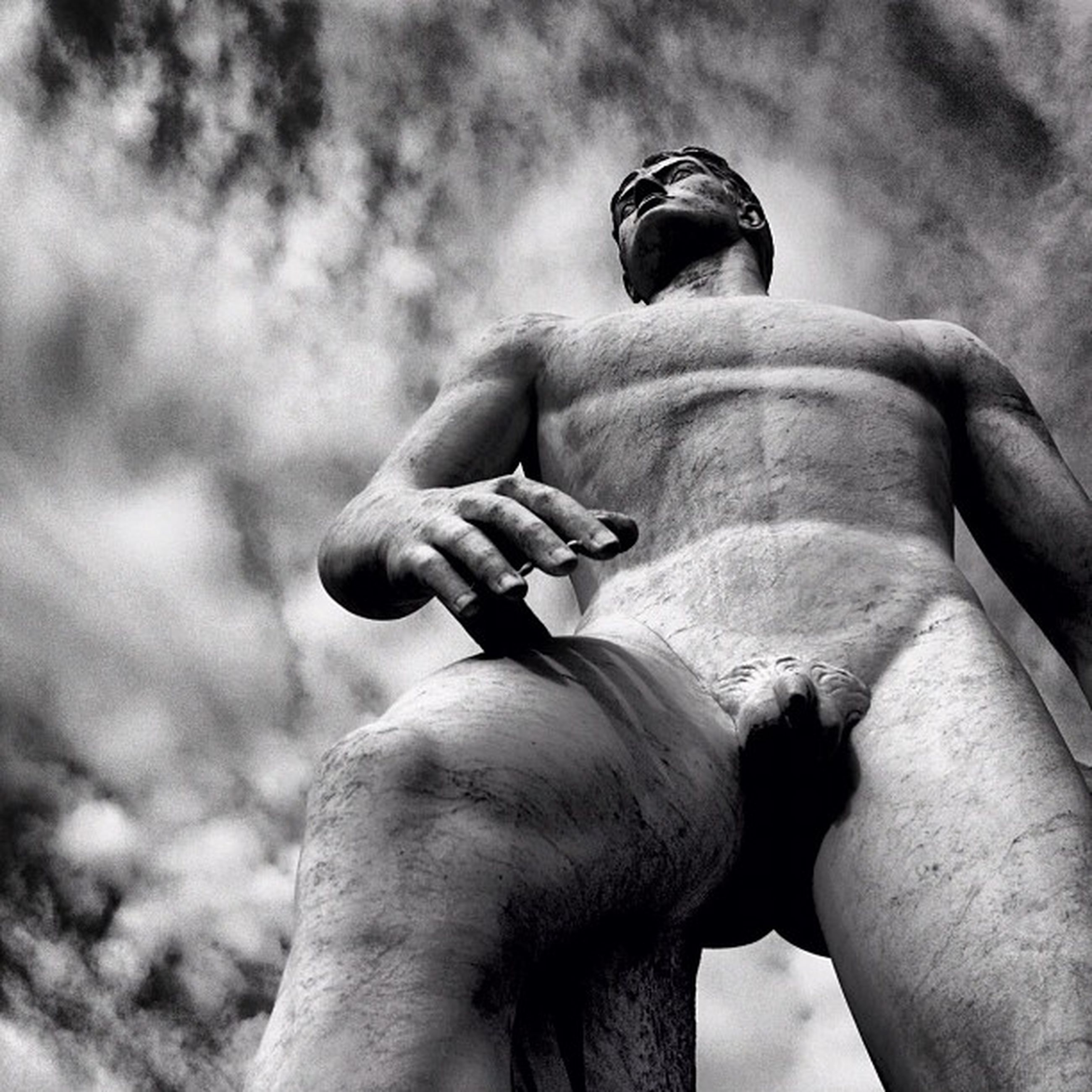 sky, low angle view, cloud - sky, cloudy, person, statue, sculpture, human representation, men, cloud, art and craft, holding, focus on foreground, part of, art, creativity, close-up, outdoors