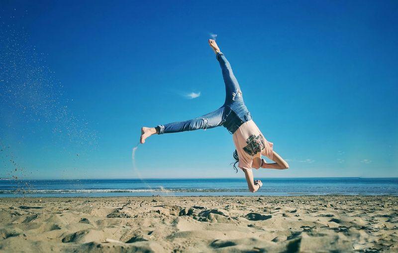 Upside down image of man on beach against blue sky
