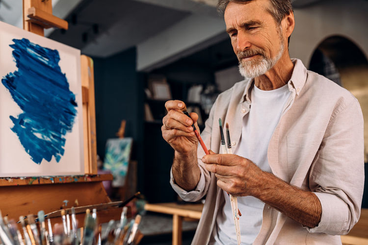 Senior man with paintbrush at workshop