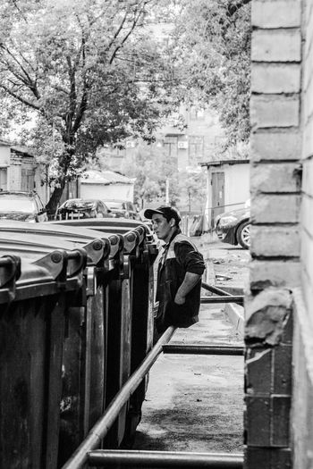 Portrait of garbage man Architecture Building Exterior Built Structure Casual Clothing City Day Leisure Activity Lifestyles Men Nature One Person Outdoors Plant Railing Real People Rear View Standing Three Quarter Length Tree