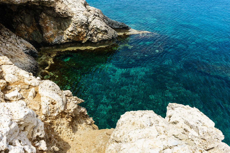 Blue Lagoon with rocky coast in Ayia Napa Rock Rock - Object Solid Water Beauty In Nature Sea Rock Formation Tranquility Nature Scenics - Nature Tranquil Scene Blue High Angle View Day Turquoise Colored No People Land Idyllic Outdoors Shallow