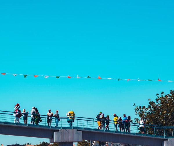 People walking against blue sky