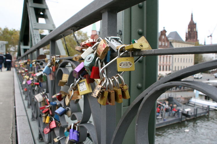 Padlocks on bridge over river in city
