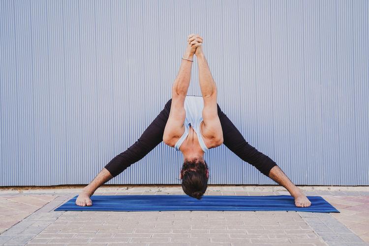Full length of man doing yoga on exercise mat against wall