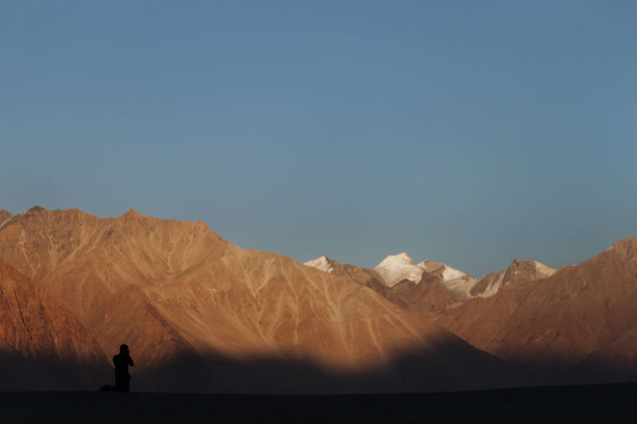 a photographer capturing the sun setting on the mountains Himalayas India Sunset Silhouettes Arid Climate Beauty In Nature Clear Sky Day Desert Landscape Men Mountain Mountain Range Nature One Person Outdoors People Real People Salt Flat Scenics Silhouette Sky Standing Tranquil Scene Tranquility Water